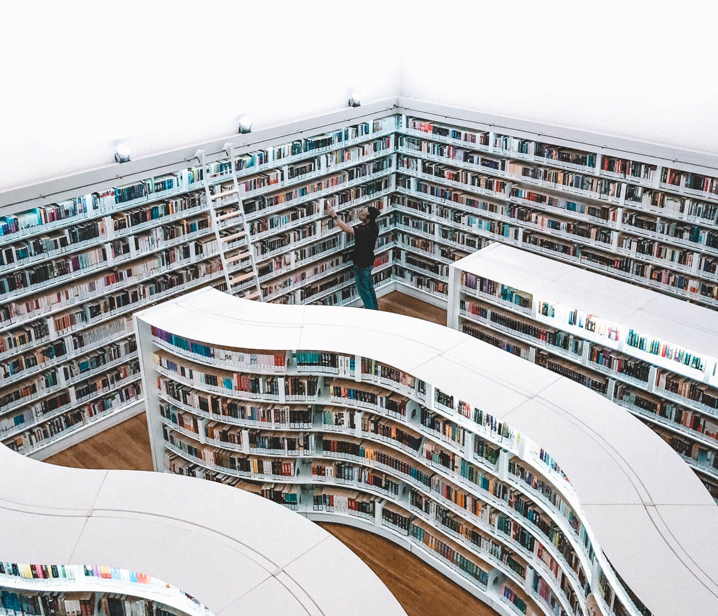 a photo with a man searching something in a curved library