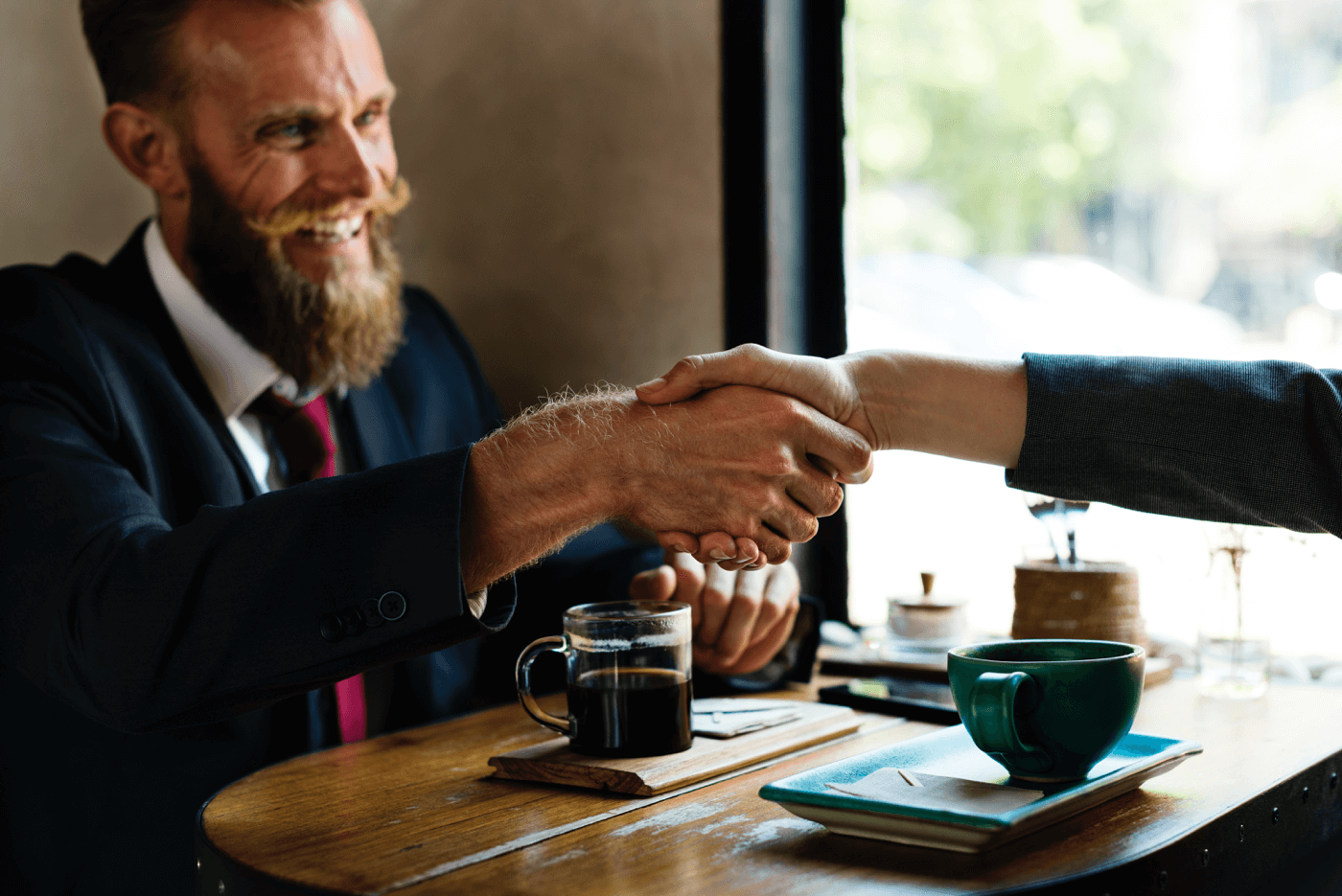 a man with a beard shaking hand with someone at the desk