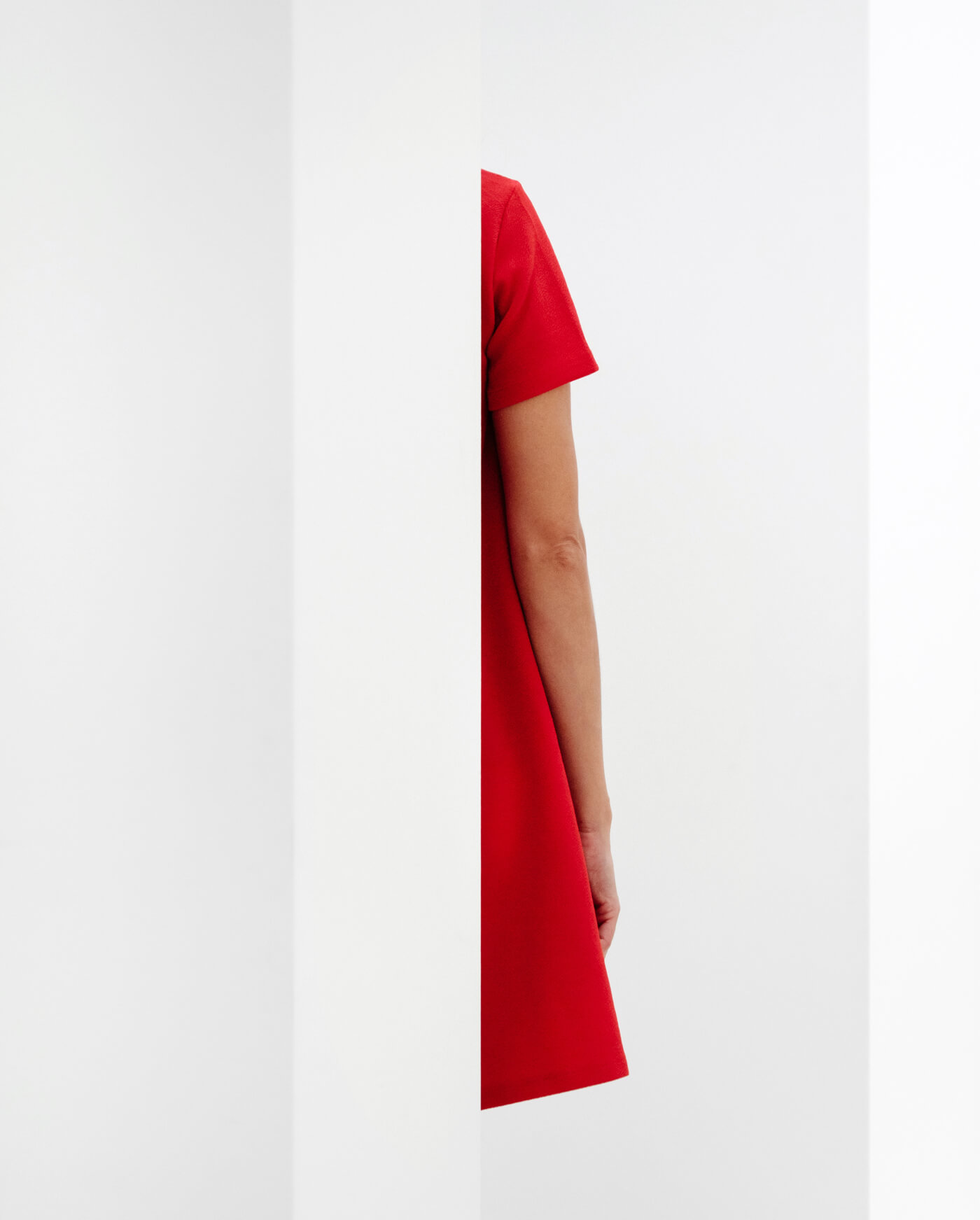 a half-seen woman in red dress on a white background