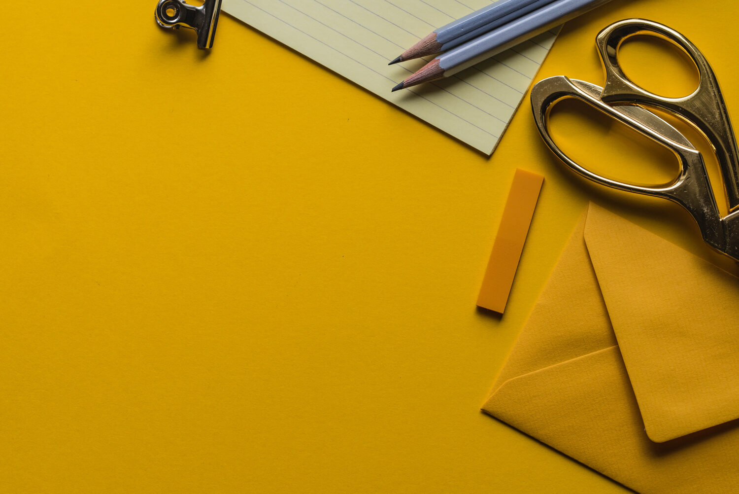 a photo of scissors, notebook and envelopes at the yellow background