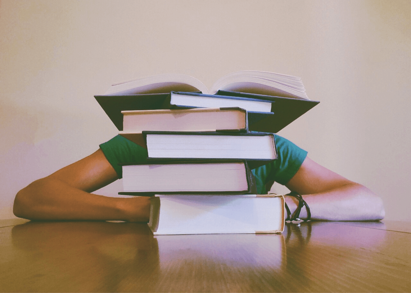 a pile of books and a person behind